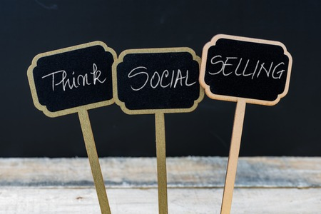 Business message THINK SOCIAL SELLING written with chalk on wooden mini blackboard labels, defocused chalkboard and wood table in background