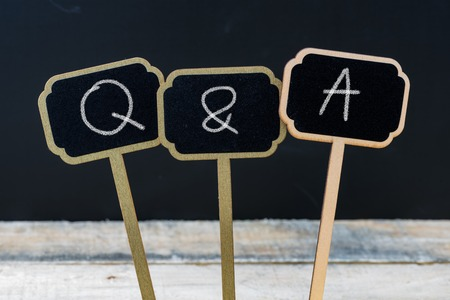Business message Q & A as QUESTIONS and ANSWERS written with chalk on wooden mini blackboard labels, defocused chalkboard and wood table in background