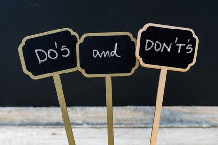 ビジネスメッセージDO'SとDON'Sは、木製のミニ黒板のラベルにチョークで書かれた、背景に黒板と木製のテーブルの焦点を当てていない 写真素材 - 67247800