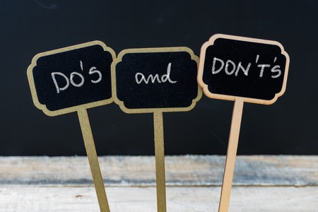 Business message DO'S and DON'T'S written with chalk on wooden mini blackboard labels, defocused chalkboard and wood table in background