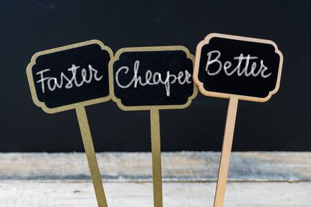 cheaper: Business message Faster, Cheaper, Better written with chalk on wooden mini blackboard labels, defocused chalkboard and wood table in background