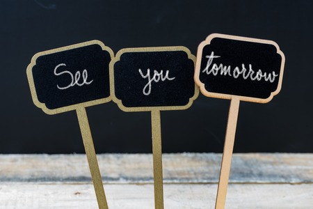 Business message See You Tomorrow written with chalk on wooden mini blackboard labels, defocused chalkboard and wood table in background Foto de archivo