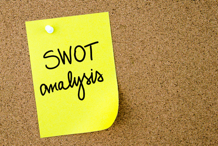 swot analysis: SWOT Analysis text written on yellow paper note pinned on cork board with white thumbtack. Business concept image with copy space available Stock Photo
