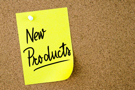 new products: New Products text written on yellow paper note pinned on cork board with white thumbtack. Business concept image with copy space available