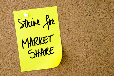 strive: Strive For Market Share text written on yellow paper note pinned on cork board with white thumbtack. Business concept image with copy space available