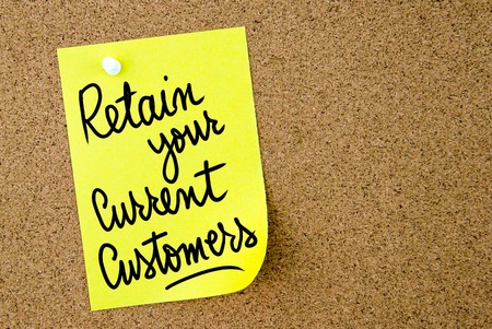 retain: Retain Your Current Customers text written on yellow paper note pinned on cork board with white thumbtack. Business concept image with copy space available Stock Photo