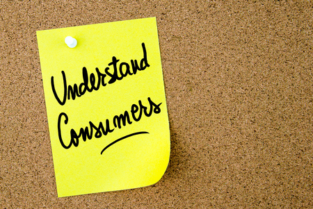 understand: Understand Consumers text written on yellow paper note pinned on cork board with white thumbtack. Business concept image with copy space available