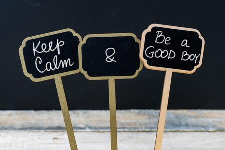 good boy: Keep Calm and Be A Good Boy message written with chalk on mini blackboard labels, defocused chalkboard and wooden table in background. Fun and humor concept