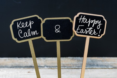 easter message: Keep Calm and Happy Easter message written with chalk on mini blackboard labels, defocused chalkboard and wooden table in background. Fun and humor concept Stock Photo