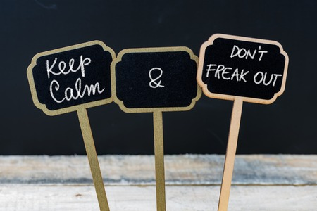 freak out: Keep Calm and Do Not Freak Out message written with chalk on mini blackboard labels, defocused chalkboard and wooden table in background. Fun and humor concept