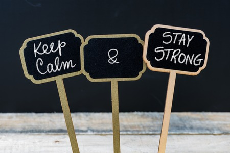 strong message: Keep Calm and Stay Strong message written with chalk on mini blackboard labels, defocused chalkboard and wooden table in background. Fun and humor concept
