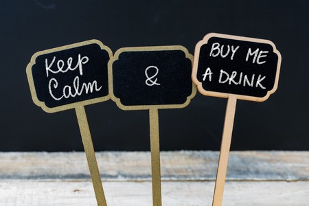 drink me: Keep Calm and Buy Me A Drink message written with chalk on mini blackboard labels, defocused chalkboard and wooden table in background. Fun and humor concept
