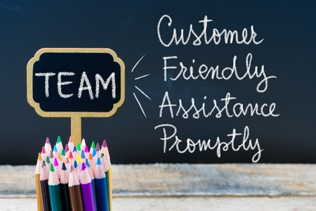 promptly: Business Acronym TEAM Customer Friendly Assistance Promptly written with chalk on wooden mini blackboard labels and chalkboard background.