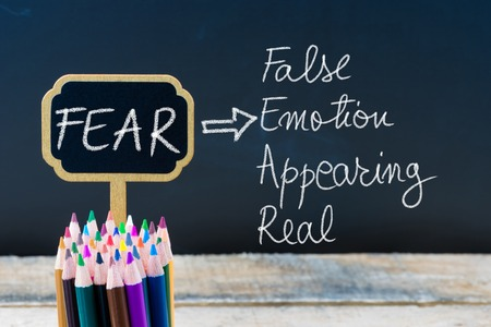 appearing: Business Acronym FEAR False Emotion Appearing Real written with chalk on wooden mini blackboard labels and chalkboard background.