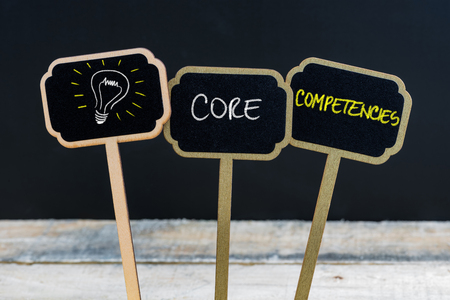 Concept message CORE COMPETENCIES and light bulb as symbol for idea written with chalk on wooden mini blackboard labels, defocused chalkboard and wood table in background
