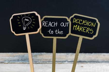 reach out: Concept message REACH OUT to the DECISION MAKERS and light bulb as symbol for idea written with chalk on wooden mini blackboard labels, defocused chalkboard and wood table in background