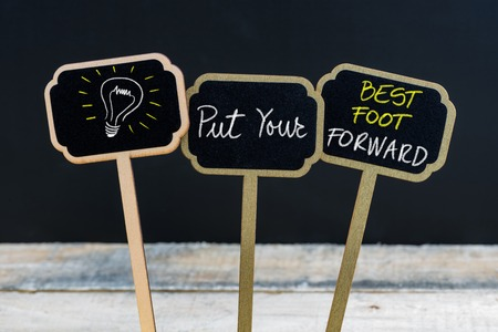 put forward: Concept message PUT YOUR BEST FOOT FORWARD and light bulb as symbol for idea written with chalk on wooden mini blackboard labels, defocused chalkboard and wood table in background