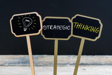 pensamiento estrategico: Concepto mensaje de pensamiento estratégico y la bombilla como símbolo de la idea por escrito con tiza en la pizarra las mini etiquetas de madera, pizarra y desenfocado mesa de madera en el fondo Foto de archivo
