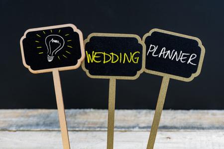 Concept bericht WEDDING PLANNER en gloeilamp als symbool voor idee geschreven met krijt op houten mini blackboard etiketten, defocused krijtbord en houten tafel op de achtergrond