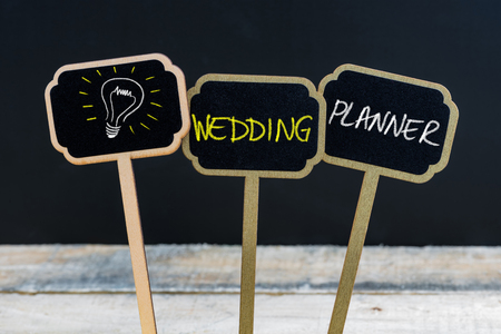 Concept message WEDDING PLANNER and light bulb as symbol for idea written with chalk on wooden mini blackboard labels, defocused chalkboard and wood table in background