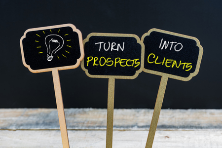 turn table: Concept message TURN PROSPECTS INTO CLIENTS and light bulb as symbol for idea written with chalk on wooden mini blackboard labels, defocused chalkboard and wood table in background Stock Photo