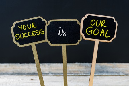 Concept message YOUR SUCCESS IS OUR GOAL written with chalk on wooden mini blackboard labels, defocused chalkboard and wood table in background