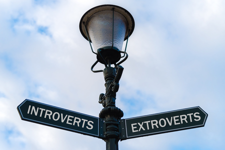 Street lighting pole with two opposite directional arrows over blue cloudy background. Introverts versus Extroverts concept.
