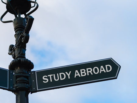 Street lighting pole with conceptual message STUDY ABROAD on directional arrow over blue cloudy background.