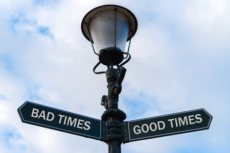 bad times: Street lighting pole with two opposite directional arrows over blue cloudy background. Bad Times versus Good Times concept.