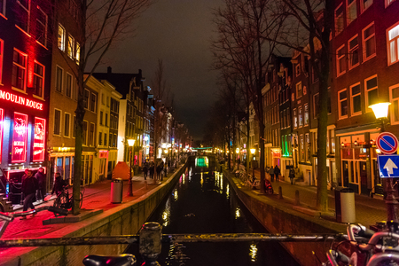 Amsterdam, Netherlands - January 9, 2017: Night street view in Amsterdam Red Light District, Netherlands. Red light district is known for legal sex work in Amsterdam and is a large tourist attraction.