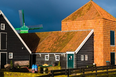 holland windmill: Zaanse Schans, Netherlands - January 10, 2017: Rural Dutch scenery with water canals in Zaanse Schans village known for well-preserved historic windmills and row houses near Amsterdam, Netherlands.