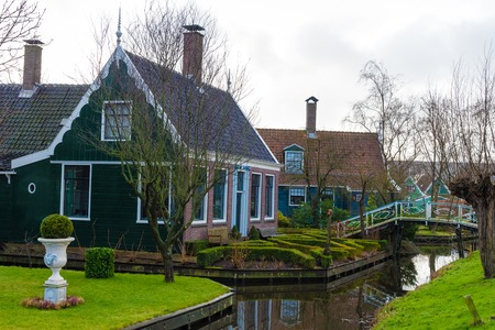 Zaanse Schans, Netherlands - January 10, 2017: Rural Dutch scenery with water canals in Zaanse Schans village known for well-preserved historic windmills and row houses near Amsterdam, Netherlands.