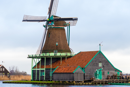 zaan: Zaanse Schans, Netherlands - January 10, 2017: Rural Dutch scenery with water canals in Zaanse Schans village known for well-preserved historic windmills and row houses near Amsterdam, Netherlands.