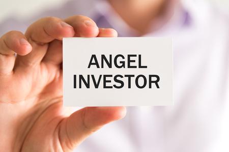 エンジェル投資家、ビジネス コンセプト イメージ ソフト フォーカスの背景のテキストとカードを持っている実業家でクローズ アップ