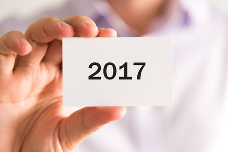 advise: Closeup on businessman holding a card with text year 2017, business concept image with soft focus background Stock Photo