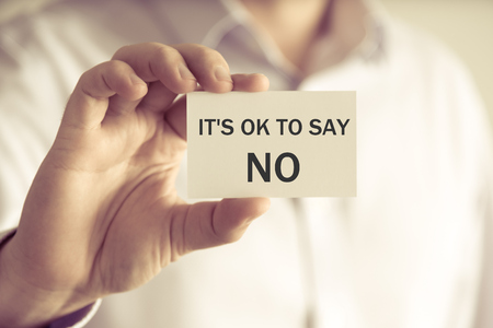 Closeup on businessman holding a card with text ITS OK TO SAY NO, business concept image with soft focus background and vintage tone Stock Photo