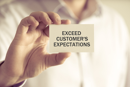 Closeup on businessman holding a card with text EXCEED CUSTOMERS EXPECTATIONS, business concept image with soft focus background and vintage tone