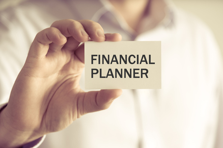 Closeup on businessman holding a card with text FINANCIAL PLANNER, business concept image with soft focus background and vintage tone