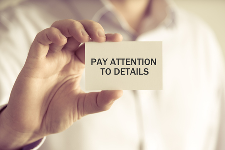 prestar atencion: Closeup on businessman holding a card with text PAY ATTENTION TO DETAILS, business concept image with soft focus background and vintage tone