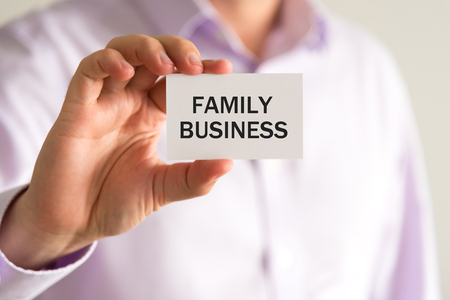 advise: Closeup on businessman holding a card with text FAMILY BUSINESS, business concept image with soft focus background