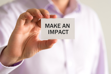 Closeup on businessman holding a card with text MAKE AN IMPACT, business concept image with soft focus background
