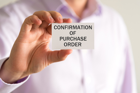 confirmacion: Closeup on businessman holding a card with text CONFIRMATION OF PURCHASE ORDER, business concept image with soft focus background Foto de archivo