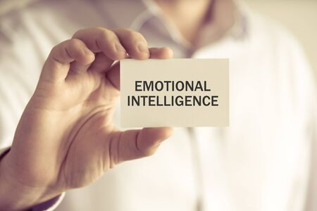 inteligencia emocional: Closeup on businessman holding a card with text EMOTIONAL INTELLIGENCE, business concept image with soft focus background and vintage tone Foto de archivo