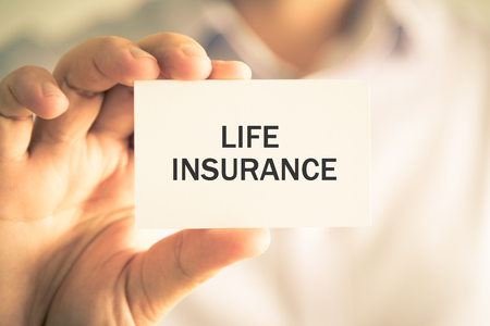 advise: Closeup on businessman holding a card with text LIFE INSURANCE, business concept image with soft focus background and vintage tone