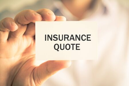 Closeup on businessman holding a card with text INSURANCE QUOTE, business concept image with soft focus background and vintage tone Stock Photo