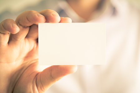 Closeup on businessman holding white empty message card with copy space for text, business concept image with soft focus background and vintage tone