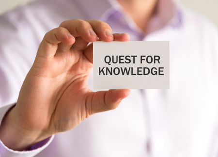 Closeup on businessman holding a card with QUEST FOR KNOWLEDGE message, business concept image with soft focus background and vintage tone