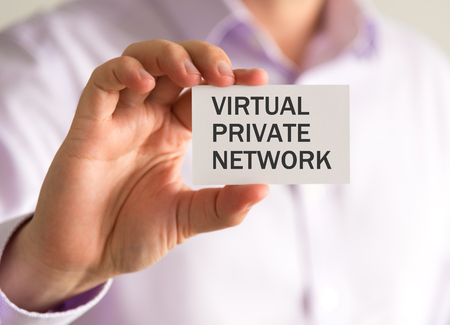Closeup on businessman holding a card with VPN VIRTUAL PRIVATE NETWORK message, business concept image with soft focus background and vintage tone
