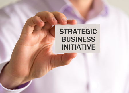 Closeup on businessman holding a card with STRATEGIC BUSINESS INITIATIVE message, business concept image with soft focus background and vintage tone