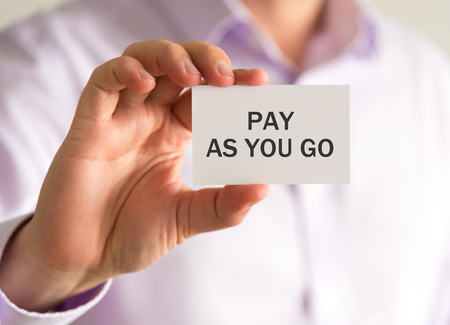 Closeup on businessman holding a card with PAY AS YOU GO message, business concept image with soft focus background and vintage tone Imagens